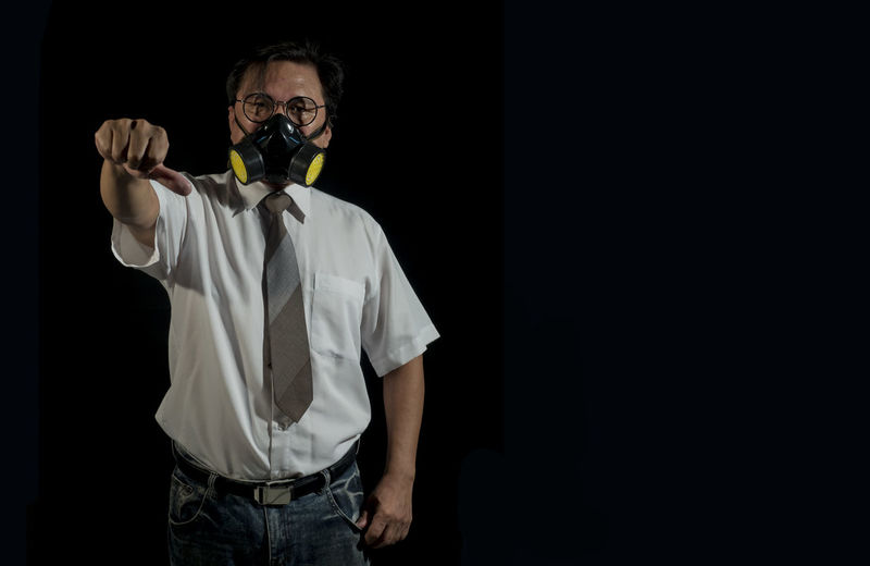 Portrait of businessmen wearing gas masks with a black background. Concept of pollution world Dirty Dangerous Contamination Gas Mask Lifestyles Protective Workwear Unpleasant Smell Warming Uncertainty  Unhygienic Safety