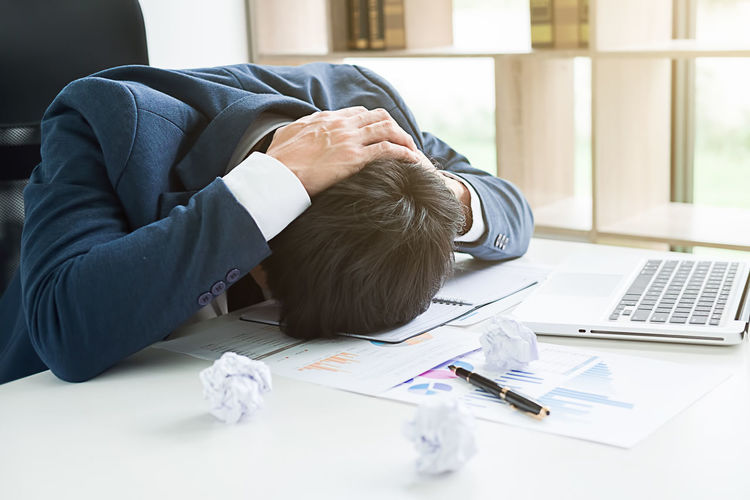 Stressed Businessman Resting Head On Desk In Office