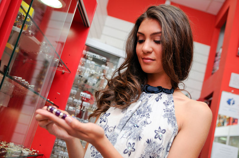 Portrait of attractive young woman buying a bracelet at a jewelry Shopping Adult Beautiful Woman Brown Hair Casual Clothing Contemplation Front View Hair Hairstyle Holding Jewelry Leisure Activity Lifestyles Long Hair One Person Portrait Real People Shop Standing Waist Up Women Young Adult Young Women
