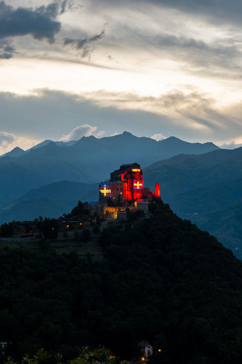 High angle view of illuminated building by mountains against sky