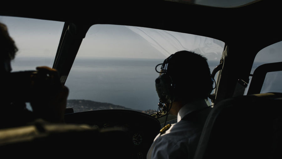 Rear view of pilot sitting in cockpit of airplane