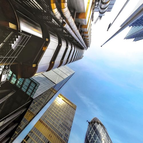 Directly below shot of modern buildings against sky in city