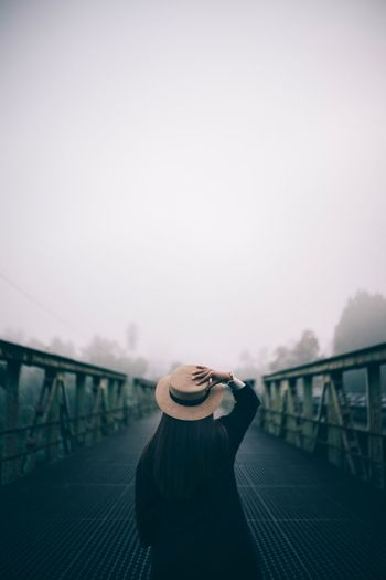 Alone Hat One Person Real People Clothing Rear View Railing Lifestyles Standing Bridge Built Structure