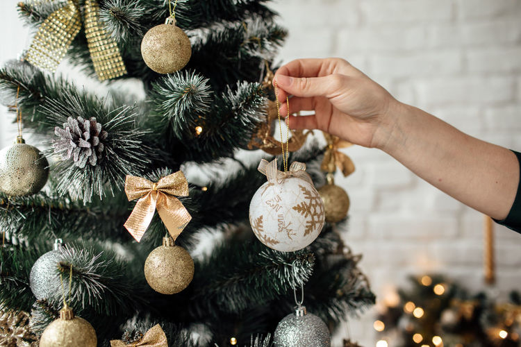 Cropped image of woman holding christmas ornament by tree