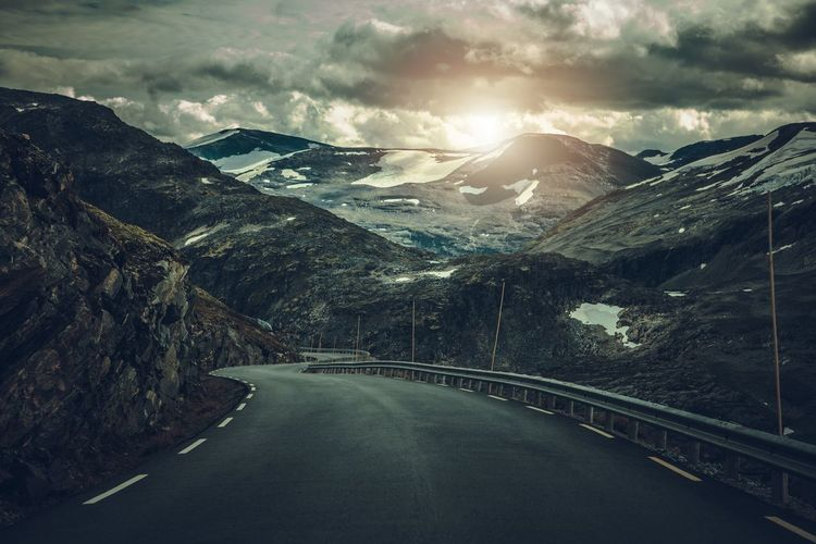 Dramatic Alpine Road in Norway. Raw Rocky Landscape and the Winding Road. Alpine Dramatic Sky Norway Road Beauty In Nature Cloud - Sky Cold Temperature Crash Barrier Diminishing Perspective Direction Environment Landscape Mountain Mountain Range Nature No People Non-urban Scene Norwegian Outdoors Road Scenery Scenics Scenics - Nature Sky Snow The Way Forward Tranquility Transportation Winter