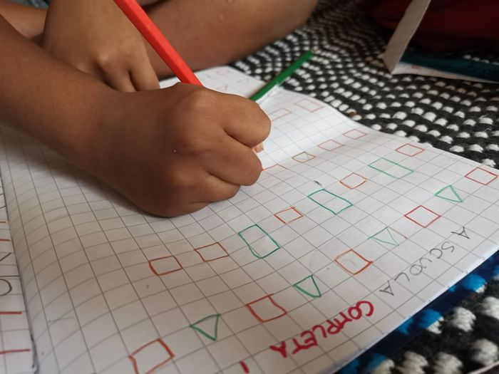 High angle view of child writing in book