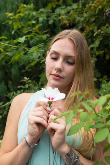 Young woman looking at flower while standing against plants
