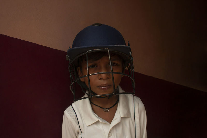 Portrait of boy wearing sports helmet against wall
