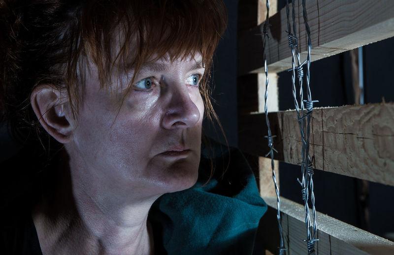 Close-up of depression senior woman looking through wood