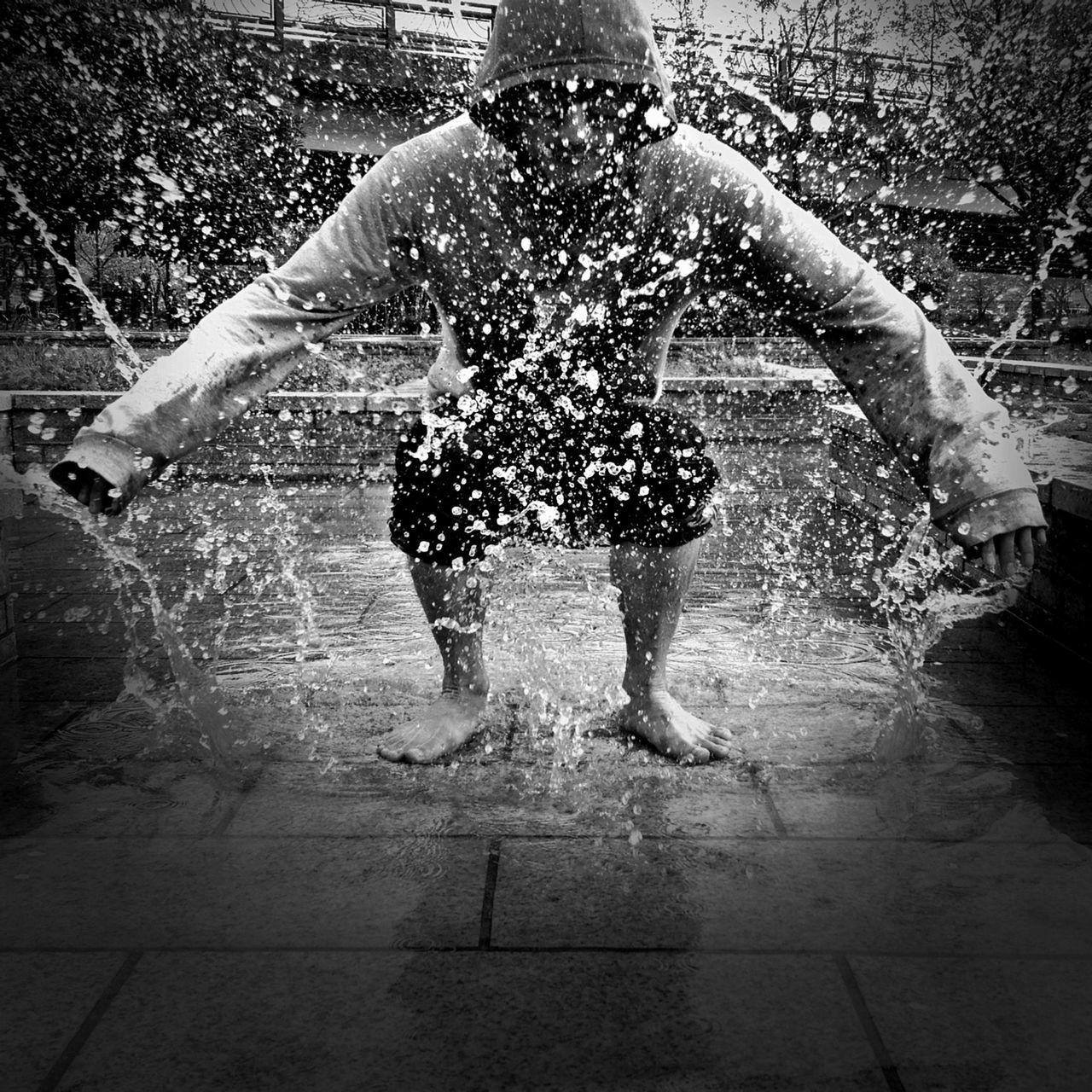 Man under splashing water outdoors