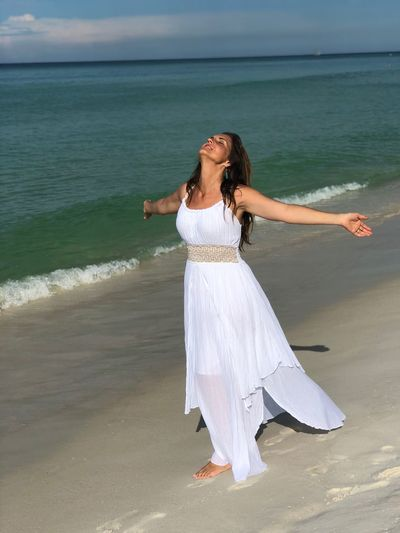 Woman With Arms Outstretched Standing On Shore At Beach