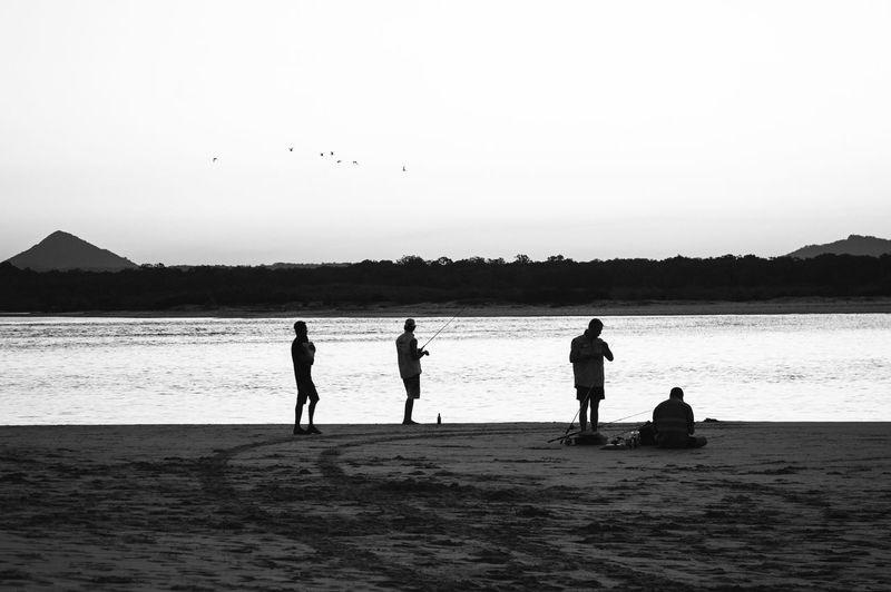 People fishing at calm sea