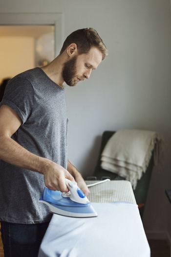 Midsection of man holding sofa at home