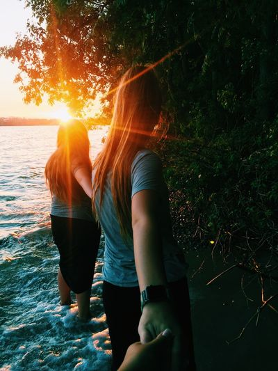 Sun flares. Natural Wildlife Wilderness Calm Beautiful Love Ocean Lake Beach Two People Togetherness Love Outdoors Young Women Women Men Nature Young Adult Water Vacations Sea Adult People Tree Adults Only Sunset Real People Day Friendship