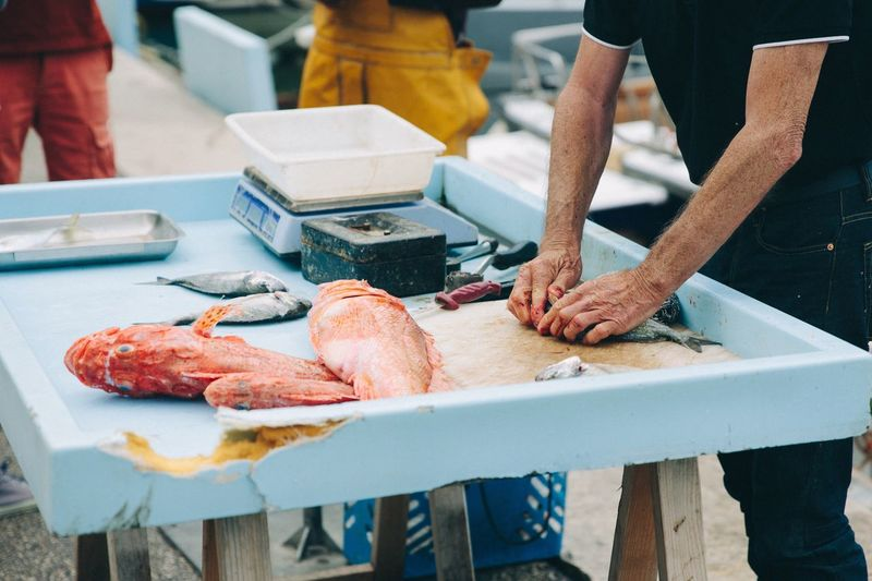 Man slicing fishes at market stall