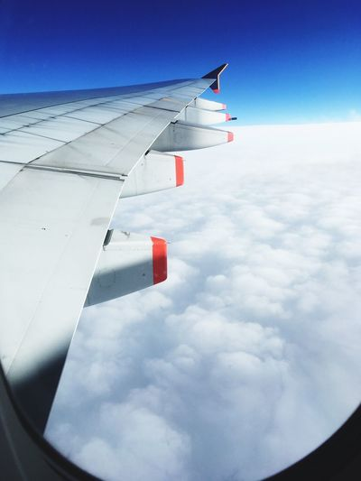 Aircraft wing against sky seen through window