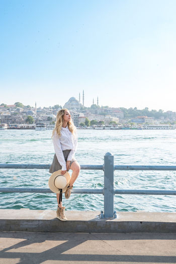 Beautiful woman sitting on railing by sea against clear sky
