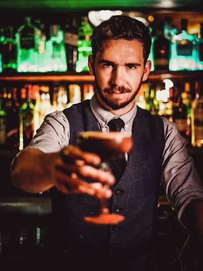 Portrait of bartender holding drink while standing in bar