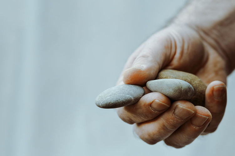 Cropped Hand Of Man Holding Stones