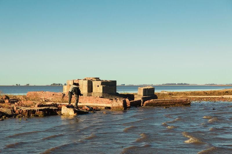 Old ruin on beach against clear sky