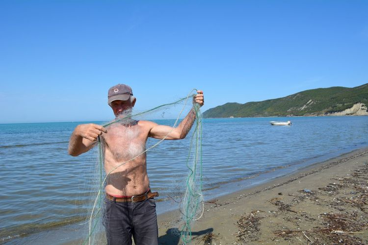 Shirtless Fisherman Holding Net While Standing Against Sea At Beach