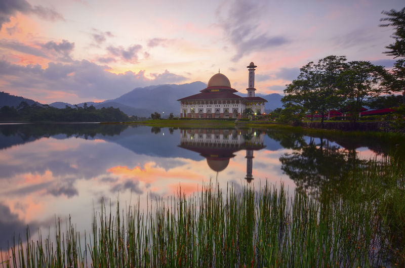 Reflection of temple in lake during sunset