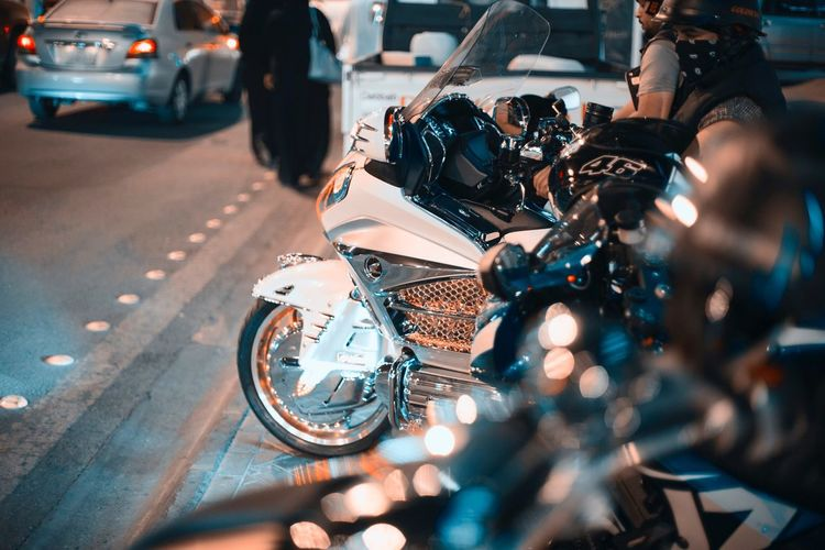 Side view of man sitting on motorcycle at street during night