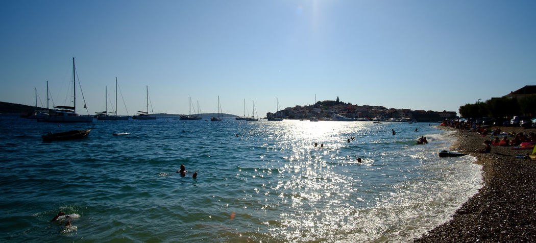 Primosten, Croatia Primošten Beach Beauty In Nature Blue Clear Sky Day Horizon Over Water Jet Boat Leisure Activity Lifestyles Men Nature Nautical Vessel One Person Outdoors Paddleboarding Real People Sailboat Scenics Sea Sky Swimming Vacations Water Waterfront Wave