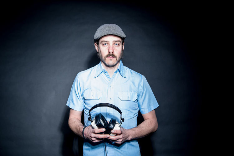 Clichéd 70s DJ studio shot 70s Adult Beard Black Background Cap Disco Dj Headphones Looking At Camera Mustache One Man Only One Person Retro Sideburns Studio Shot