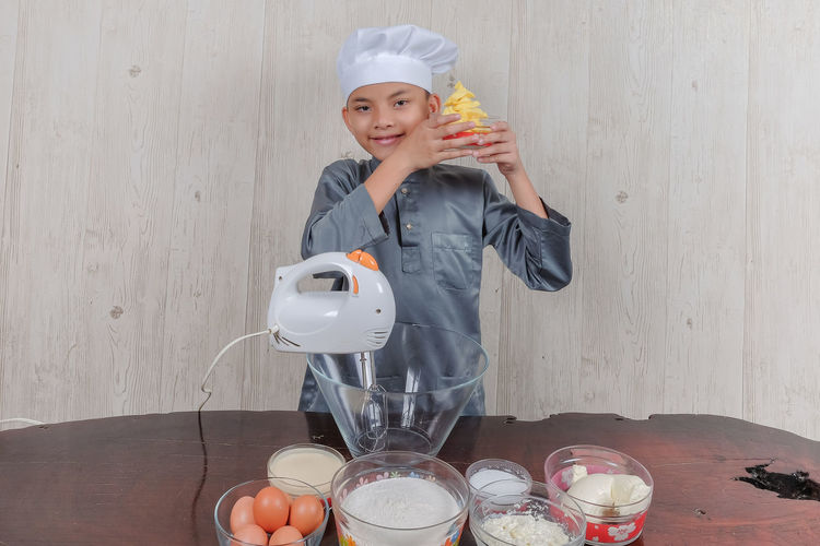 Portrait of boy wearing chef hat with ingredients on table standing against wall at home