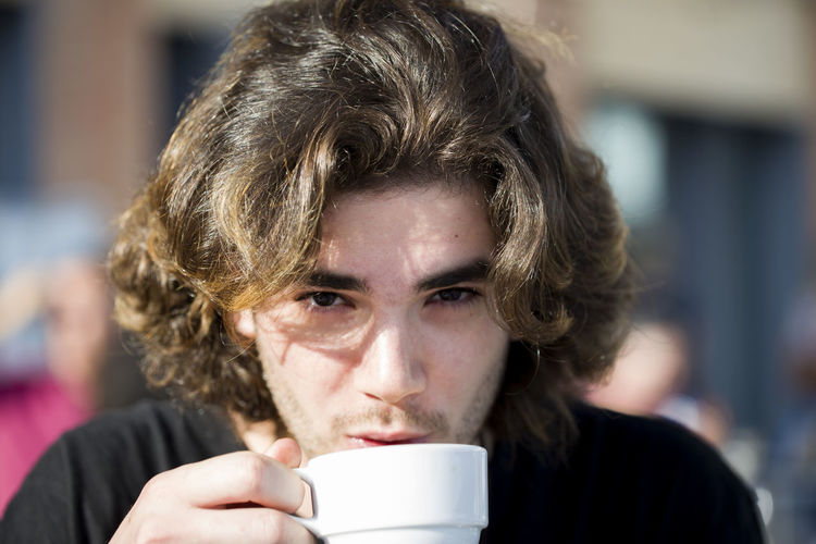 Portrait of a young man with long hair who drinks coffee in a street cafe on a summer sunny day Drinking Coffee Looking At Camera Tea Adult Close-up Coffee - Drink Coffee Cup Cup Day Drink Drinking Focus On Foreground Food And Drink Headshot One Man Only One Person Outdoors People Portrait Real People Young Adult Young Men