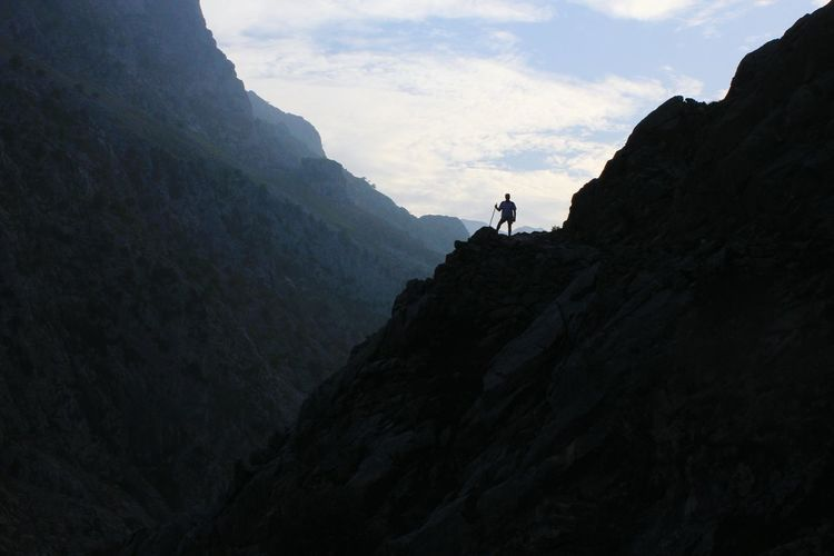 Low angle view of man standing on mountain
