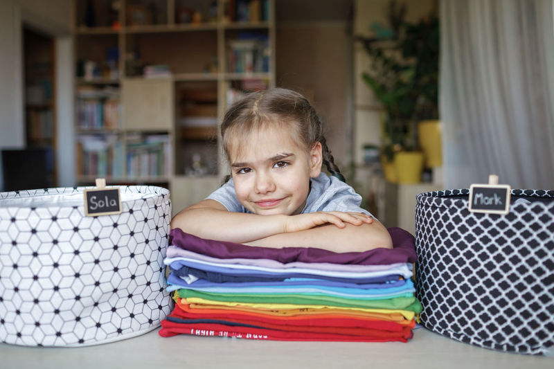 Portrait of smiling girl with folded clothes at home