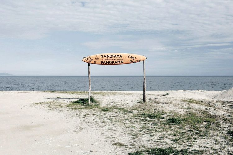 Information sign on beach against sky