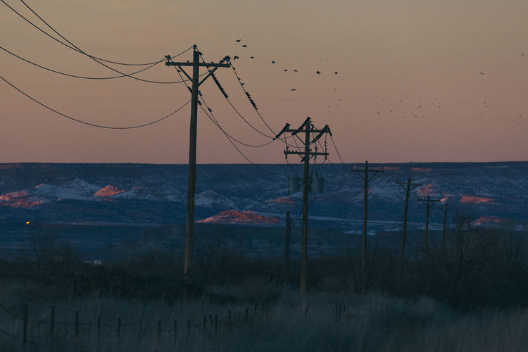 Scenic view of electricity poles against sky during sunset