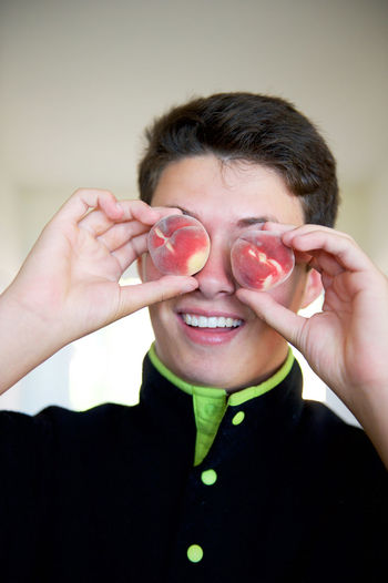 Boy holding peaches over eyes