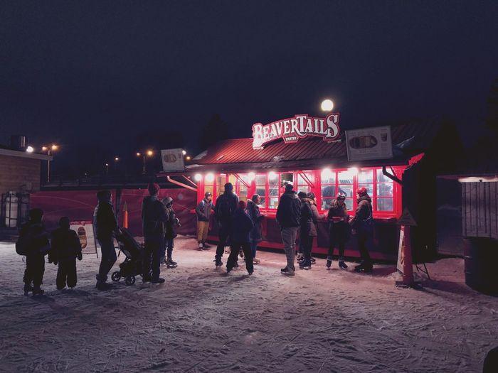 People at illuminated market in city at night