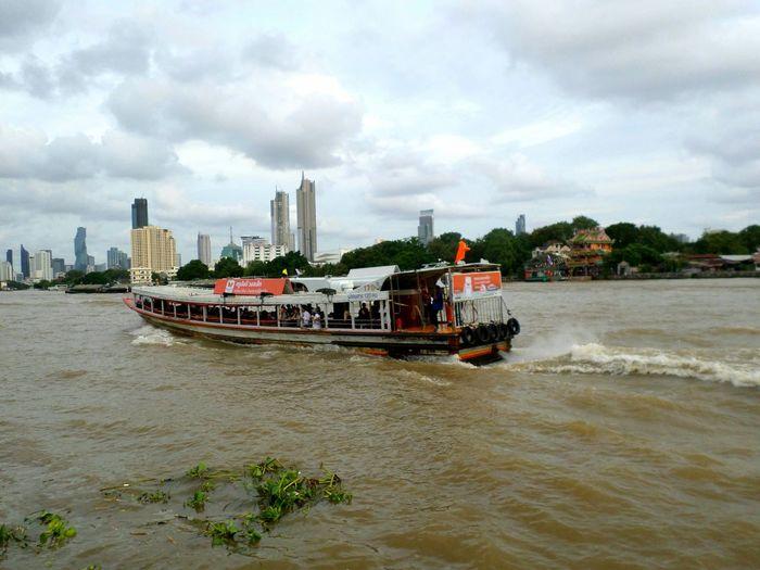 Boat in sea against sky in city
