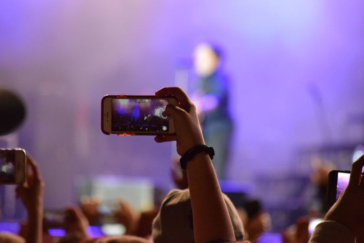 Cropped Image Of Woman Photographing Musician On Stage