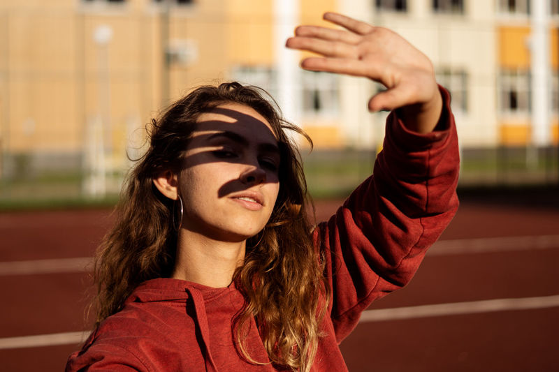 Portrait of young woman shielding eyes at running track