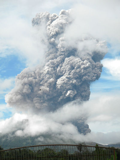 Aerial view of volcanic landscape against cloudy sky