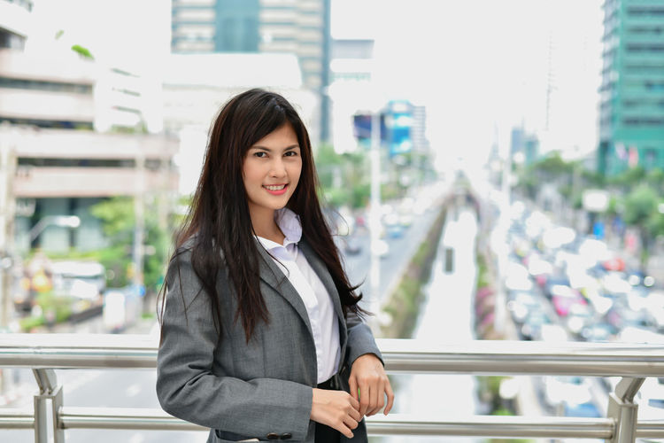 Business Concept. Young businessmen are expressing emotions in the city. Asian businesswoman standing in business district. Asian business woman is happy in the city. Adult ASIA Asian  Background Beautiful Beauty Building Business Businesspeople Businesswoman Caucasian Cheerful Chinese Confident  Elegant Emotion Executive  Female Formal Happiness Happy Insurance Japanese  Life Lifestyle Looking Manager Mature Meeting Modern Office Outdoor People Plan Portrait Professional Smile Standing Style Success Successful Suit Team Teamwork Thai White Woman Work Worker Young