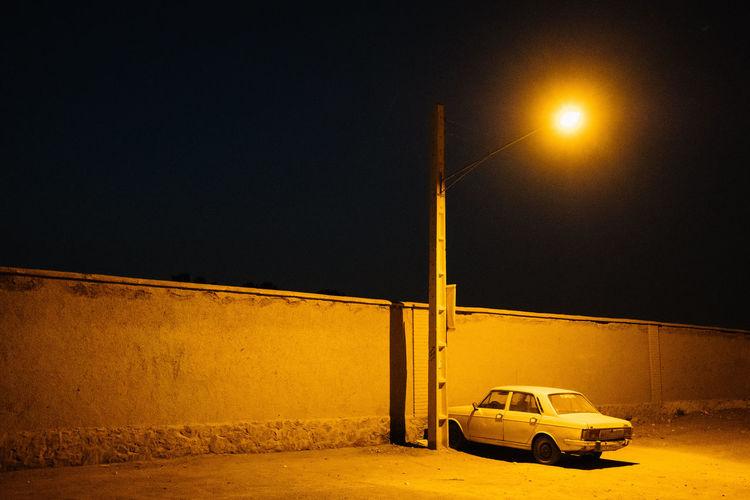 Car on illuminated street against clear sky at night