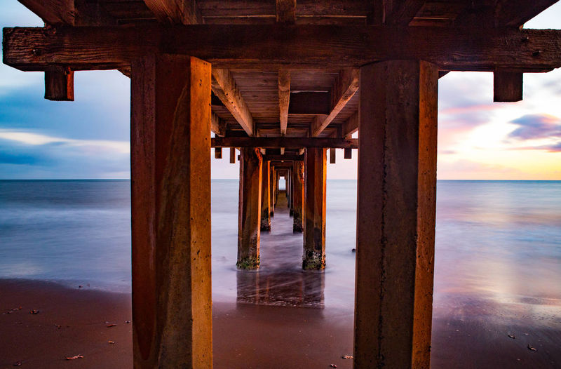 Underneath view of pier on sea against sky during sunset
