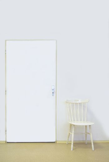 Empty chair on table against white wall