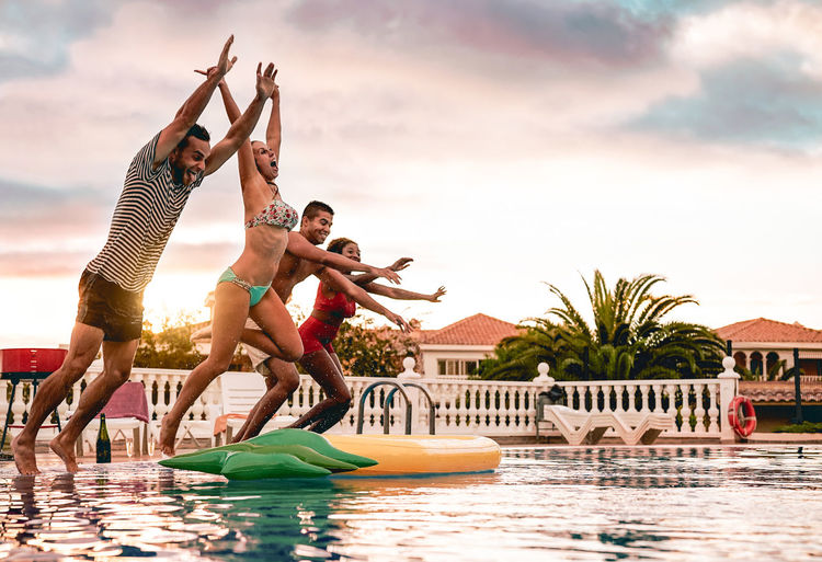 Friends jumping in swimming pool against sky