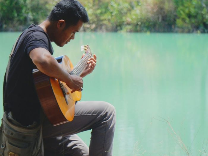 Side view of young man playing guitar in lake