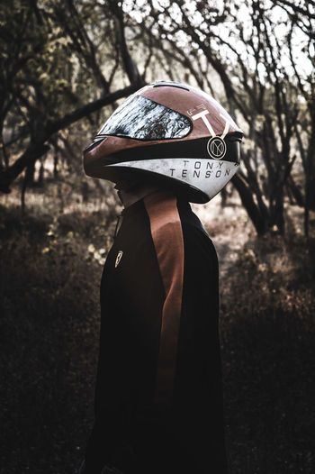 Side View Of Man Wearing Helmet While Standing Against Trees In Forest
