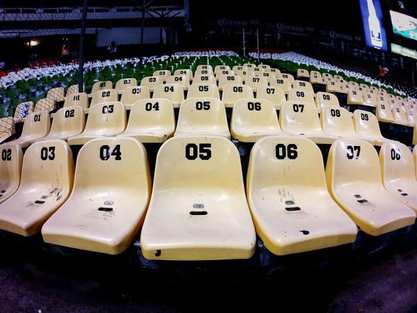 General view of the seats inside the stadium Sports Court Sports Complex Stadium Seats Alphabet Communication In A Row Text Close-up Large Group Of Objects Abundance Information Side By Side Repetition Many Order Arrangement