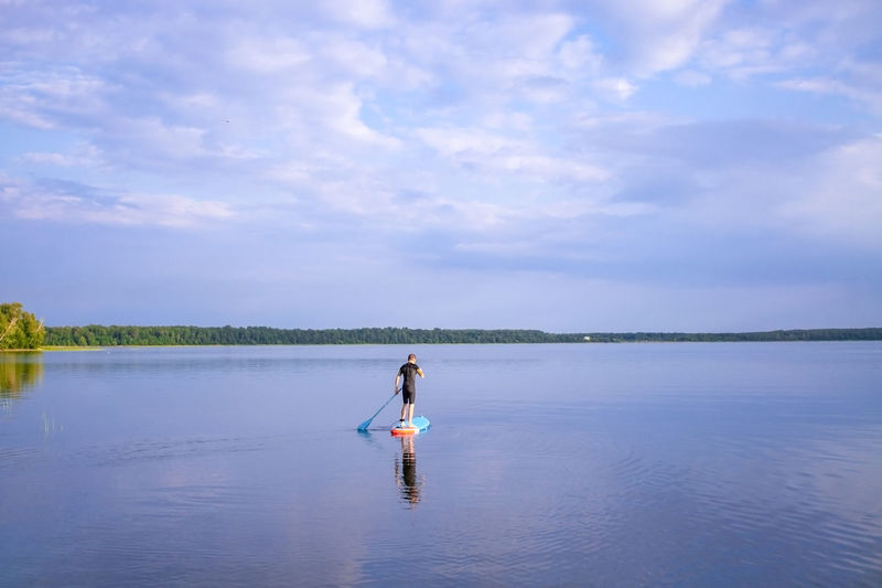 Man is paddling on a sup board on the lake. lake landscape and blue cloudy sky.